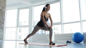 Full längd av den sportive kvinnan som gör övningar lager videofilmer