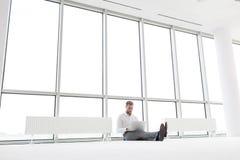 Full längd av den unga affärsmannen som använder bärbara datorn, medan sitta under element mot fönster på kontoret arkivfoto