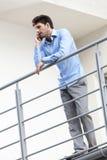 Full längd av den unga affärsmannen som använder mobiltelefonen på hotellbalkongen Royaltyfri Fotografi