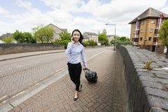 Full längd av den unga asiatiska affärskvinnan med bagage, medan svara mobiltelefonen som går på trottoaren Fotografering för Bildbyråer