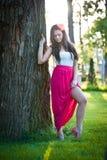 Full längd av den unga caucasian kvinnlign med långt rött kjolanseende nära det utomhus- trädet arkivfoto