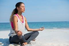 Full längd av den unga kvinnan som mediterar på stranden Royaltyfri Bild