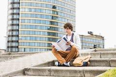 Full längd av den unga manliga högskolestudentläseboken mot byggnad arkivfoton