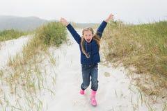 Full längd av en gladlynt flickaspring på stranden Arkivbild
