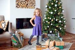 Full längd av en le liten flicka i en purpurfärgad klänning som poserar i lyxig vardagsrum nära spisen i bakgrunden arkivfoton