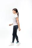 Full längd av en ung kvinna som går över vit bakgrund Arkivbilder