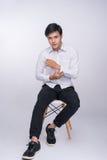 Full längd av ett ungt asiatiskt tillfälligt mansammanträde på en stol över royaltyfri fotografi