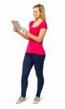 Full längd av kvinnan som använder den Digital minnestavlan Arkivfoto