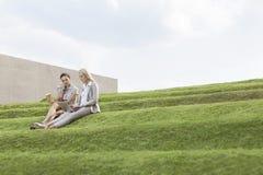 Full längd av kvinnliga affärsledare med disponibelt sammanträde för kaffekopp och bärbar datorpå gräsmoment mot himmel Arkivbilder