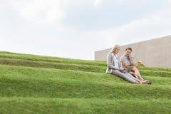 Full längd av kvinnliga affärsledare med disponibelt sammanträde för kaffekopp och bärbar datorpå gräsmoment mot himmel Arkivbild