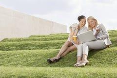 Full längd av lyckliga affärskvinnor som ser bärbara datorn, medan sitta på gräsmoment royaltyfria foton