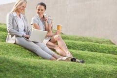 Full längd av lyckliga affärskvinnor som ser bärbara datorn, medan sitta på gräsmoment mot väggen Royaltyfri Fotografi