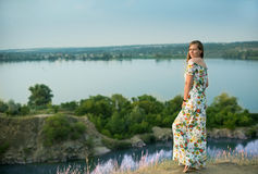 Full längd av lyckligt le för charmig positiv iklädd lång vit sommarklänning för kvinna i solnedgångbakgrund Royaltyfri Bild