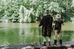 Full längd av män som står på flodbanken arkivbild