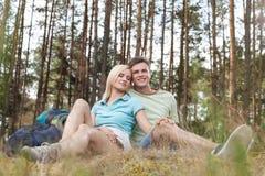 Full längd av romantiska unga fotvandra par som kopplar av i skog Arkivfoton