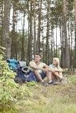 Full längd av unga fotvandra par med ryggsäckar som kopplar av i skog Royaltyfri Fotografi
