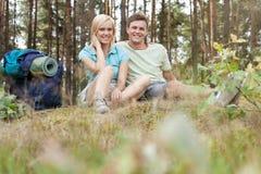Full längd av unga fotvandra par med ryggsäcken som kopplar av i skog Royaltyfria Foton