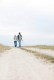 Full längd av unga fotvandra par som går på banan på fältet Arkivfoton
