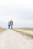 Full längd av unga fotvandra par som går på banan på fältet Royaltyfria Bilder