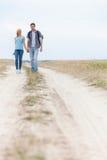 Full längd av unga fotvandra par som går på slinga på fältet Royaltyfria Foton