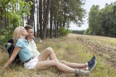 Full längd av unga fotvandra par som kopplar av i skog Arkivfoton