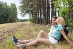 Full längd av unga fotvandra par som kopplar av i skog Royaltyfria Bilder