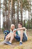 Full längd av unga fotvandra par som kopplar av i skog Arkivbilder