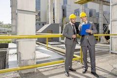 Full längd av unga manliga arkitekter som ser skrivplattan på konstruktionsplats royaltyfri bild