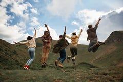 Full längd av upphetsat folk som hoppar i bergen fotografering för bildbyråer