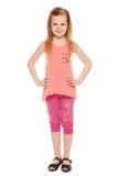 Full längd en gladlynt liten flicka i kortslutningar och en T-tröja; isolerat på den vita bakgrunden Arkivfoton