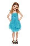 Full längd som en förtjusande liten flicka i blått klär, isolerat på den vita bakgrunden arkivbild