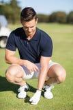 Full längdman som förlägger golfboll på utslagsplats arkivbilder