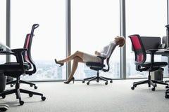 Full längdsidosikt av den unga affärskvinnan som är lutande tillbaka i stol på kontoret Royaltyfri Bild
