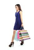 Full längdsidosikt av den unga kvinnan som går med shoppingpåsen Royaltyfri Foto