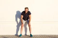 Full längdsportman som vilar mot väggen royaltyfri fotografi