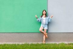Full längdstående av den härliga kvinnan i tillfällig jeansgrov bomullstvillstil i sommartid som står nära grönt och ljust - blå  royaltyfria foton