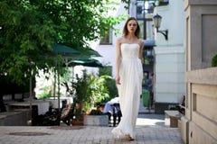 Full längdstående av den härliga modellkvinnan i den vita klänningen arkivfoton
