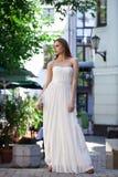 Full längdstående av den härliga modellkvinnan i den vita klänningen arkivfoto