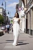 Full längdstående av den härliga modellkvinnan som går i vit D arkivbild