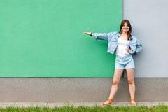 Full längdstående av den lyckliga tillfredsställda härliga kvinnan i tillfällig jeansgrov bomullstvillstil i sommartid som står n royaltyfria foton