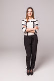 Full längdstående av den stilfulla kvinnan för smiley över grå bakgrund Royaltyfri Foto