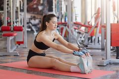 Full längdstÃ¥ende av den sunda motiverade sportwomanen som sträcker muskler, medan sitta pÃ¥ golv över simulatorbakgrund fotografering för bildbyråer