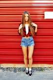 Full längdstående av det moderiktiga hipsterflickaanseendet på det rött Royaltyfria Bilder