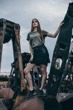 Full längdstående av det moderiktiga modeflickaanseendet på en rostig hög av metall arkivbild
