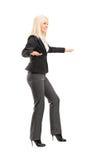Full längdstående av en affärskvinna som försöker att hålla jämvikt Arkivbild