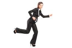 Full längdstående av en affärskvinnarunning Arkivfoto