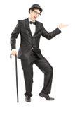 Full längdstående av en aktör i svart dräkt som gör en gest med Royaltyfri Foto