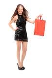 Full längdstående av en attraktiv kvinna som rymmer en shoppingpåse Arkivfoton