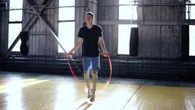 Full längdstående av en boxarebanhoppning med överhopprepet Idrotts- muskulös ung boxareutbildning med banhoppningrepet lager videofilmer