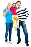 Full längdstående av en gladlynt familj av tre Fotografering för Bildbyråer